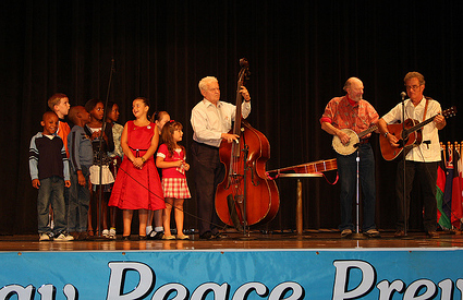 Children put on a musical performance with Pete Seeger, Chris Ruhe and a member of The Howland Wolves.