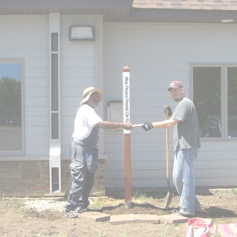 Melvin Giles (L) gifts mini Peace Pole to Josh Williams at Animal Ark Shleter
