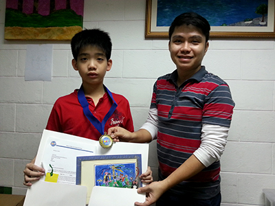 Jethro stands proudly with his Teacher displaying his prizes.
