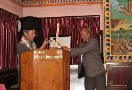 The Chairperson of the Nepal Esperanto Association receiving a small Peace Pole on behalf of the organization